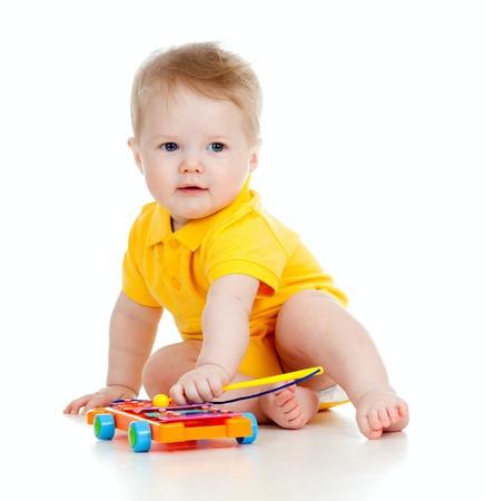 bebe gateando: chico divertido con los juguetes musicales