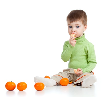 funny child eating fruits over white background photo