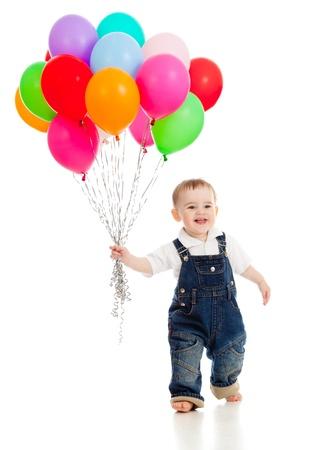 그의 손에 다채로운 풍선의 무리와 함께 아기 웃고. 흰색에 격리.