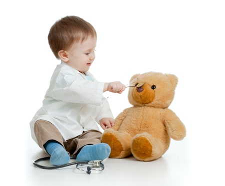 playing with spoon: Adorable boy with clothes of doctor is spoon-feeding teddy bear over white