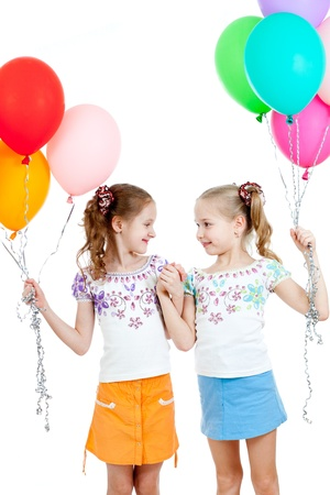 little girl smiling: Two girls  with colorful ballons in hands  Isolated on white  Stock Photo