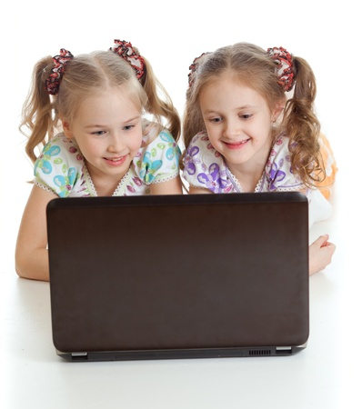 kids laptop: smart girlfriends smiling and looking at the laptop