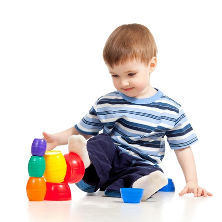 Funny little child is playing with color toys, isolated over white photo