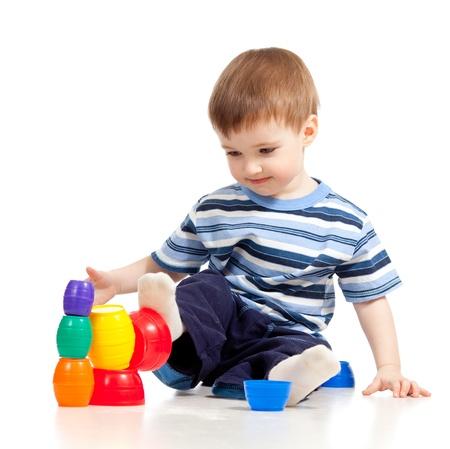 pie bebe: Gracioso niño está jugando con los juguetes de colores, aislado más de blanco