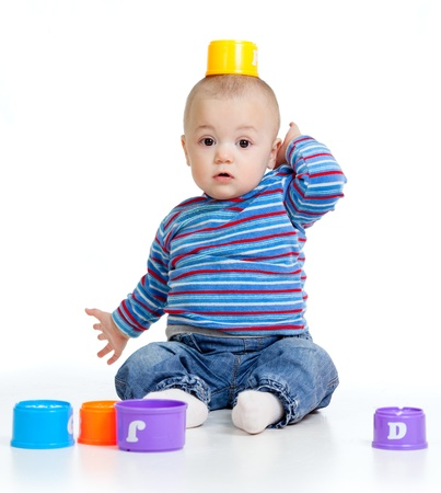 Funny little child is playing with toys, isolated over white photo
