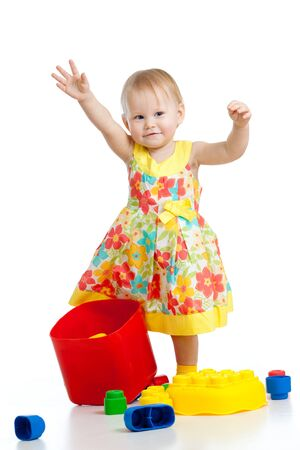 little cheerful girl with construction set over white background photo