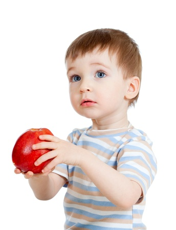 Baby boy holding and eating red apple, isolated on white photo