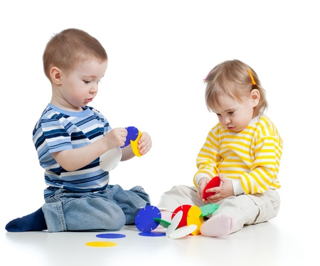 little children playing with color toy over white background photo