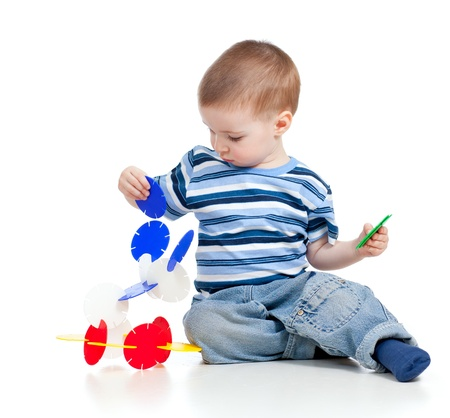 little child playing with color toy over white background photo
