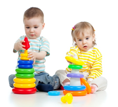 babies playing: two little children playing with color toys