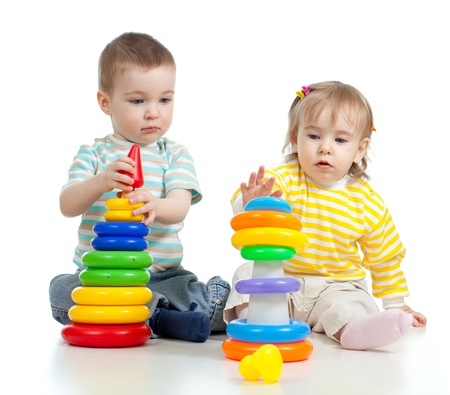 baby sitting: two little children playing with color toys