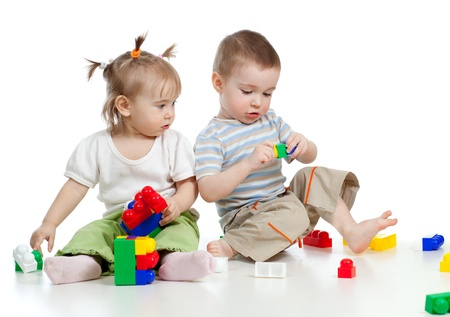 little children playing together with construction set over white background photo
