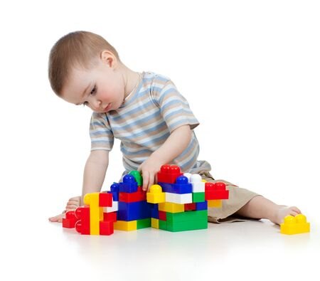little cheerful child with construction set over white background photo