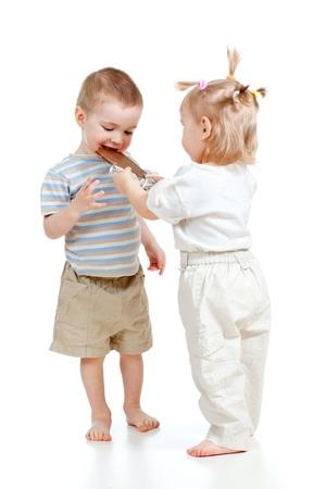 fille garçon divertir par le chocolat isolé sur blanc Banque d'images