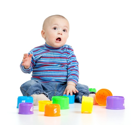 Funny baby playing with toys, isolated over white photo