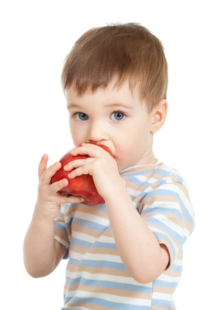Baby child holding and eating red apple, isolated on white photo