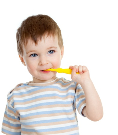 toothpaste: baby cleaning teeth and smiling, isolated on white background