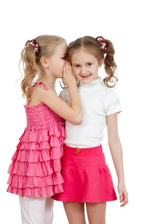 telling: Little girlfriends sharing a secret isolated on a white background