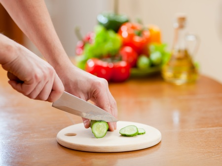 Cutting cucumber on hardboard and fresh vegetables on background  photo
