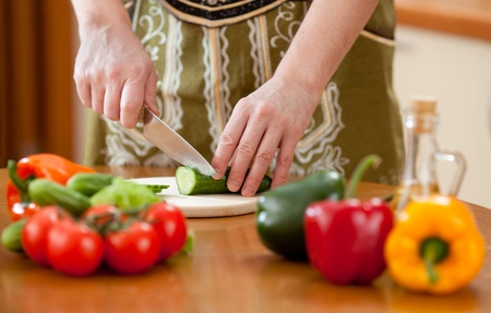 Preparing actions for vegetable salad on kitchen table  Focus on cutting cucumber Stock Photo - 12910218
