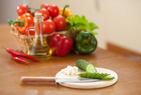Cutting cucumber and cheese on hardboard  Sunflower oil and vegetables in basket  back  photo