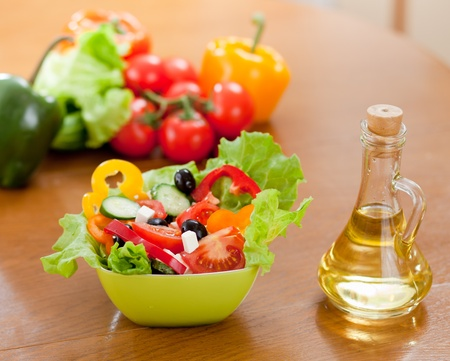 greek vegetable salad and bottle with sunflower oil on wooden table photo