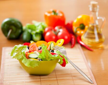 alimentos saludables: ensalada griega, las verduras y la botella con aceite de girasol en la mesa de madera