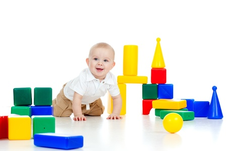 smiling baby playing among color building blocks photo