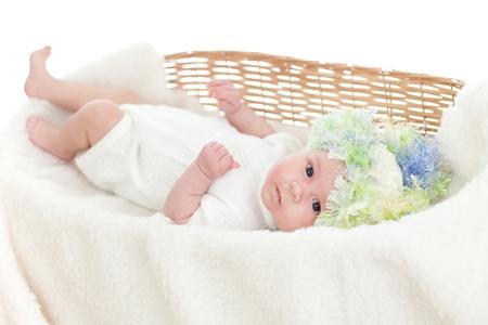 adorable baby weared cap in a wicker basket photo