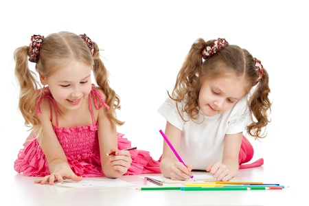 kids dress: two sisters drawing with color pencils together over white