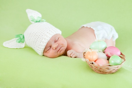 adorable baby dressed in Easter bunny cap with eggs photo