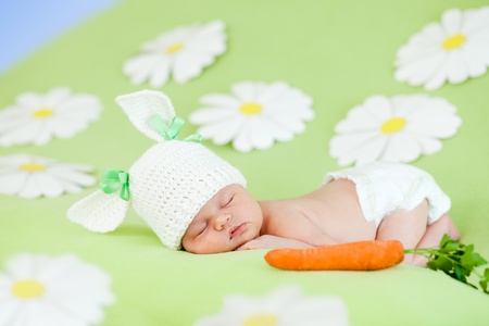 small child with a rabbit ears  Lying on his stomach with a carrot photo