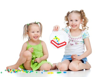 little girl sitting: children playing with color toy over white background Stock Photo