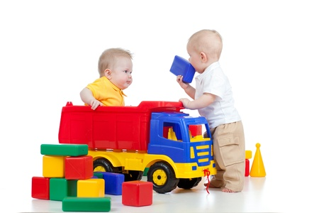 large group of objects: two little children playing with color toys