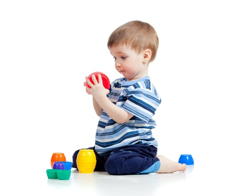 developmental: Cute little child is playing with toys while sitting on floor, isolated over white