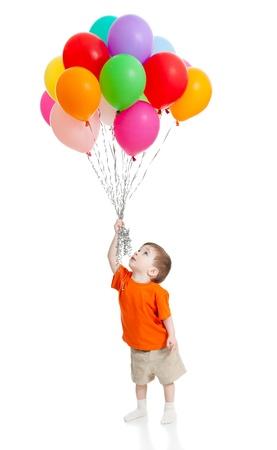彼の手に分離された白のカラフルな風船の束と笑みを浮かべて男の子