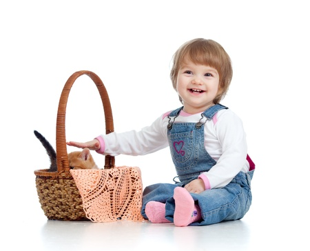 sitting down: Smiling child sitting down by basket with kittens, isolated on white Stock Photo