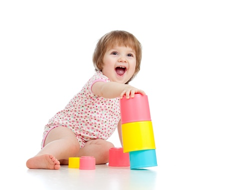 Funny little girl playing with cup toys, isolated over white photo