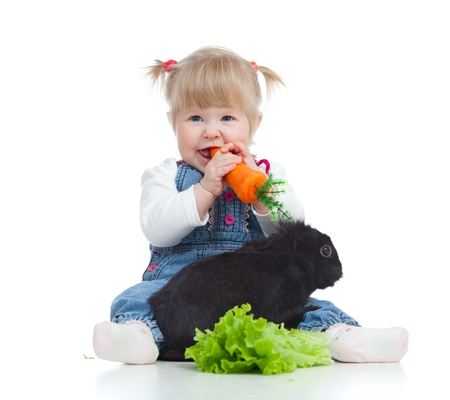 bunnie: Smiling little girl eating a carrot and feeding rabbit with lettuce on the floor