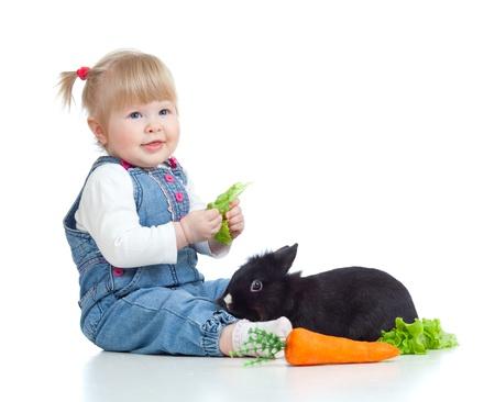 bunnie: Cute little girl feeding a rabbit with carrot and lettuce on the floor Stock Photo