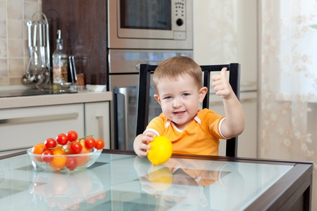 cute little boy sitting at kitchen with healthy food and showing thumb up photo