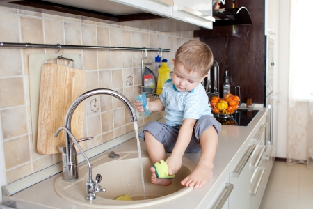 funny little boy sitting on kitchen table Stock Photo - 13171082