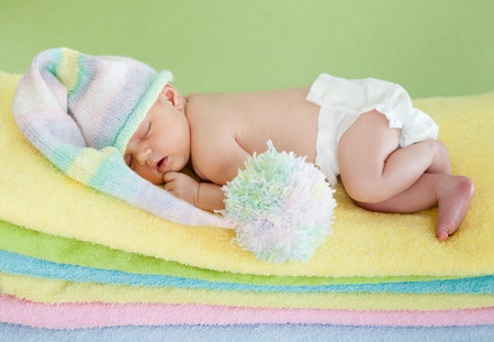 adorable baby newborn weared cap sleeping on colourful towels photo