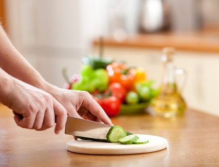 Male hands cutting of cucumer on hardboard and fresh vegetables on background photo