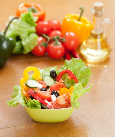 healthy greek salad, vegetables and bottle with sunflower oil as background photo