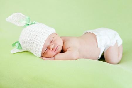 nappy: Funny sleeping newborn child  Bunny cap on head of girl  Stock Photo