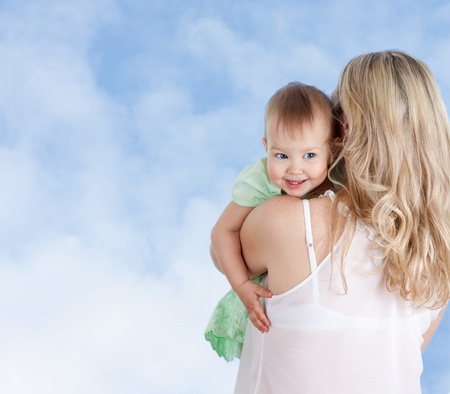 Rear view of mother with cute baby girl looking over shoulder Stock Photo - 13286731