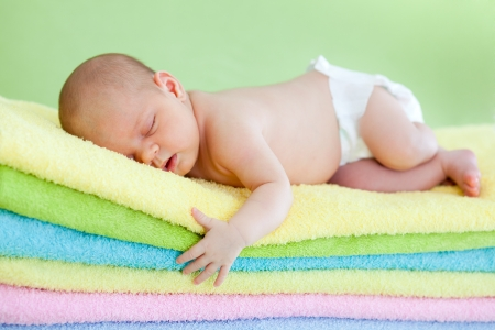 adorable baby newborn weared cap sleeping on colourful towels Stock Photo