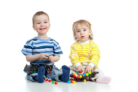 childcare: Happy children boy and girl playing together with  mosaic toy Stock Photo