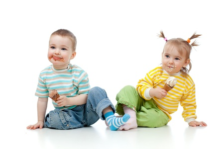 dirty faces: happy children little girl and boy with ice cream in studio isolated